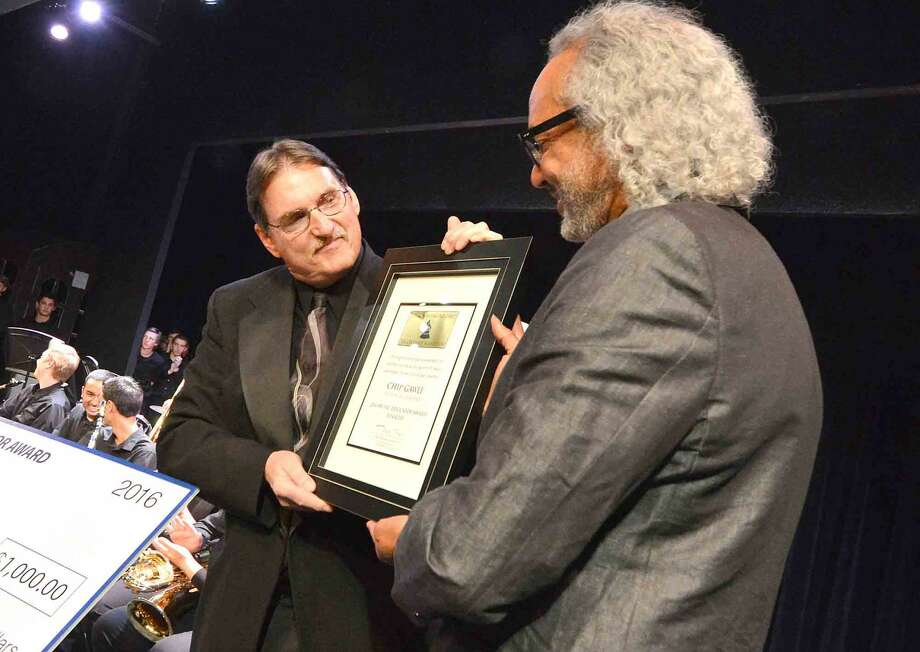 Music Teacher Chip Gawle accepts the GRAMMY Music Educator Finalist Award from Darryl Tookes who sits on the Board of Governors of the Recording Academy in New York, during a special evening of music at Wilton High Schools Little Theater on Tuesday April 26 2016 in Wilton Conn.