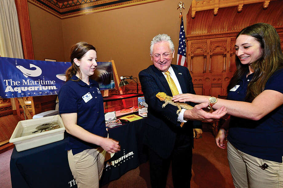 Hour photo / Erik Trautmann Norwalk Mayor Harry Rilling greets Educators Lauren Magliola and Sarah Nahabedian and a lizard from the Maritime Aquarium's new exhibit Dragons! Real or Myth? as State Senator and Majority leader Bob Duff (D-25) hosts the first-ever Norwalk Day at the Capitol Wednesday where city officials and numerous Norwalk businesses and organizations showcased Norwalk.