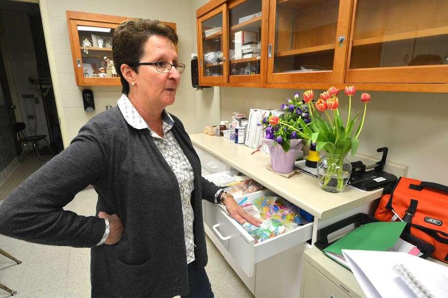 Hour Photo/Alex von Kleydorff Marvin Elementary School Nurse Kathryn McLean check some of her supplies in the Nurses Office