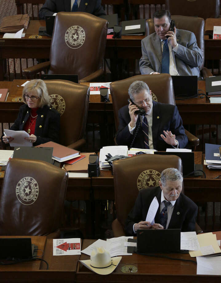 In this May 5, 2015 photo, Texas Rep. Rick Miller, R-Sugar Land, works in the House Chamber, Tuesday in Austin, Texas. Miller has filed a bill that would repeal local ordinances that ban discrimination against gay and transgender people _ attempting to roll back rules passed in many large Texas cities. The propose bill puts Miller at odds with his son, Beau Miller, who is an HIV-positive gay activist. (AP Photo/Eric Gay)