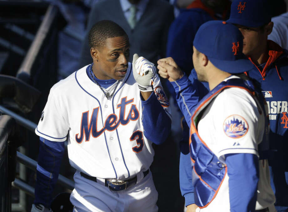New York Mets' Curtis Granderson celebrates with teammates in the dugout after hitting a walk-off sacrifice fly during the fourteenth inning of the baseball game against the Atlanta Braves at Citi Field, Sunday, April 20, 2014 in New York. The Mets defeated the Braves in extra innings 4-3. (AP Photo/Seth Wenig)