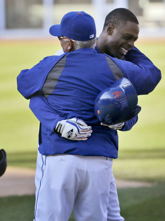 New York Mets' Curtis Granderson, right, hugs manager Terry Collins after hitting a walk-off sacrifice fly during the fourteenth inning of the baseball game at Citi Field, Sunday, April 20, 2014 in New York. The Mets defeated the Braves in extra innings 4-3. (AP Photo/Seth Wenig)