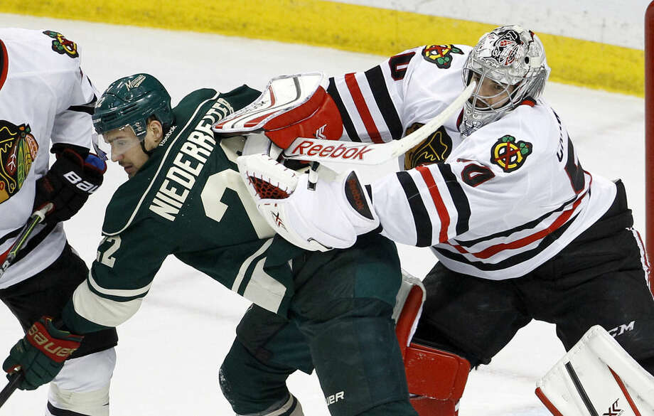 Chicago Blackhawks goalie Corey Crawford (50) clears Minnesota Wild right wing Nino Niederreiter (22), of Switzerland, away from the net during the first period of Game 3 in the second round of the NHL Stanley Cup hockey playoffs in St. Paul, Minn., Tuesday, May 5, 2015. (AP Photo/Ann Heisenfelt)
