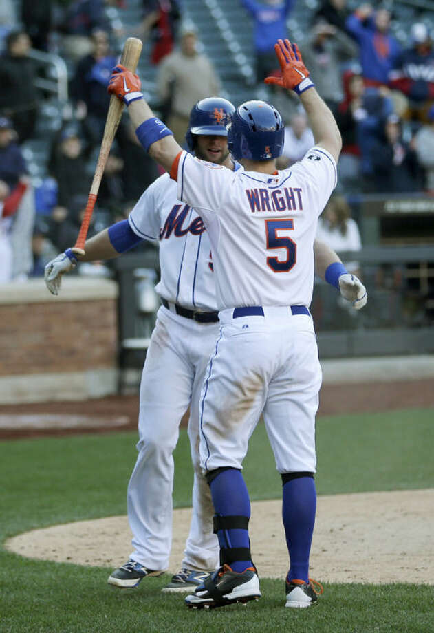 New York Mets' Kirk Nieuwenhuis, left, celebrates with David Wright after scoring on a sacrifice fly hit by Curtis Granderson during the fourteenth inning of the baseball game at Citi Field, Sunday, April 20, 2014 in New York. The Mets defeated the Braves in extra innings 4-3. (AP Photo/Seth Wenig)