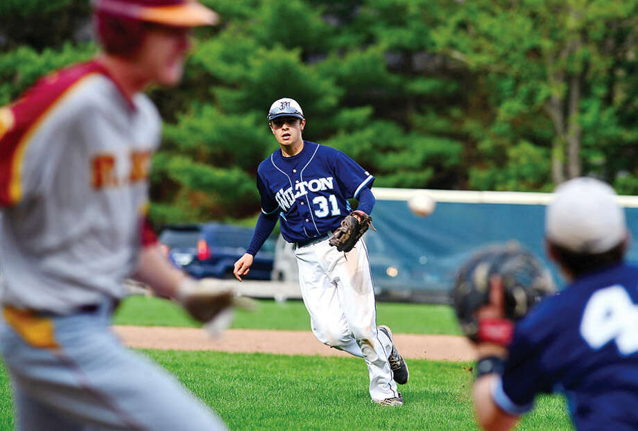 Hour photo / Erik Trautmann Wilton shortstop Dylan Lifrieri watches his throw beat out the baserunner during their game against St. Joe's Wednesday at Wilton High School.