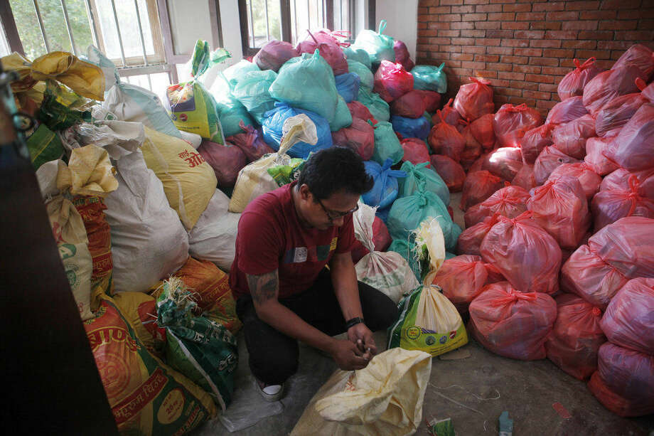 In this Tuesday, May 5, 2015 photo, a Nepalese volunteer packs food and relief material collected by Portuguese men Pedro Queiros and Lourenco Macedo Santos, to distribute among the earthquake affected in Kathmandu, Nepal. Using funds pledged through a Facebook appeal, Queiros and Santos are taking food and bedding to needy Nepalis made homeless by the magnitude 7.8 earthquake that struck just outside Kathmandu shortly before noon on April 25. (AP Photo/Niranjan Shrestha)