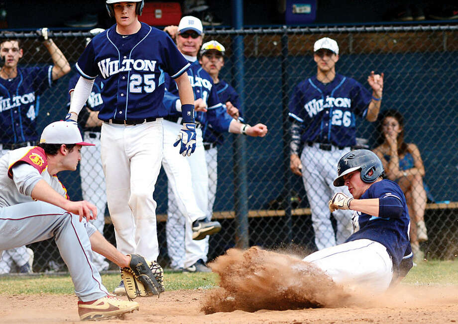 Hour photo / Erik Trautmann Wilton pitcher Jack Ward slides into home to score on a wild pitch during their game against St. Joe's Wednesday at Wilton High School.