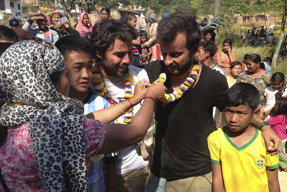 In this Tuesday, May 5, 2015 photo, a villager puts a floral garland around Portuguese Pedro Queiros, in black, with Lourenco Macedo Santos standing beside him at Ichangu Narayan on the outskirts of Kathmandu, Nepal. Using funds pledged through a Facebook appeal, Queiros and Santos are taking food and bedding to needy Nepalis made homeless by the magnitude 7.8 earthquake that struck just outside Kathmandu shortly before noon on April 25. (AP Photo/Johnson Lai)