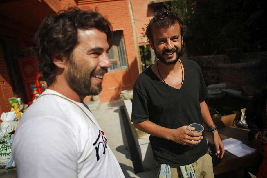 In this Tuesday, May 5, 2015 photo, Portuguese men Pedro Queiros, right, and Lourenco Macedo Santos prepare to distribute aid to the earthquake affected at the Dwarika Hotel in Kathmandu, Nepal. Using funds pledged through a Facebook appeal, Queiros and Santos are taking food and bedding to needy Nepalis made homeless by the magnitude 7.8 earthquake that struck just outside Kathmandu shortly before noon on April 25. (AP Photo/Niranjan Shrestha)