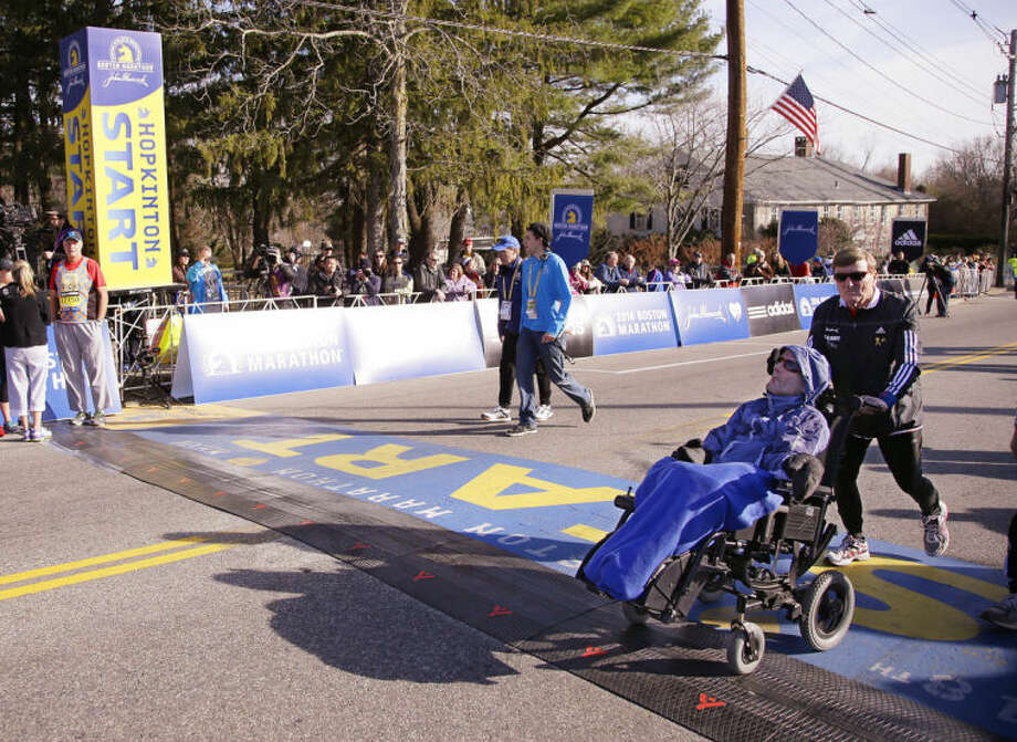 Father and son Boston Marathon race team Dick Hoyt, right, and his son Rick Hoyt walk across the start line as they warm up before they run the 118th Boston Marathon Monday, April 21, 2014 in Hopkinton, Mass. (AP Photo/Stephan Savoia)