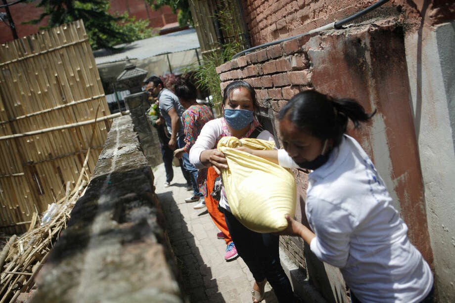 In this Tuesday, May 5, 2015 photo, Nepalese volunteers form a chain to load food and relief material collected by two Portuguese men onto a vehicle, for distribution among the earthquake affected in Kathmandu, Nepal. Using funds pledged through a Facebook appeal, two Portuguese men Pedro Queiros and Lourenco Macedo Santos are taking food and bedding to needy Nepalis made homeless by the magnitude 7.8 earthquake that struck just outside Kathmandu shortly before noon on April 25. (AP Photo/Niranjan Shrestha)
