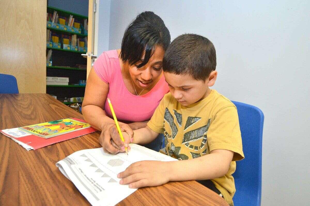 Hour Photo/Alex von Kleydorff Teacher Jatorra Patterson helps Jose Funez Espinal with some math problems during the After The Bell program at SoNo Community Center