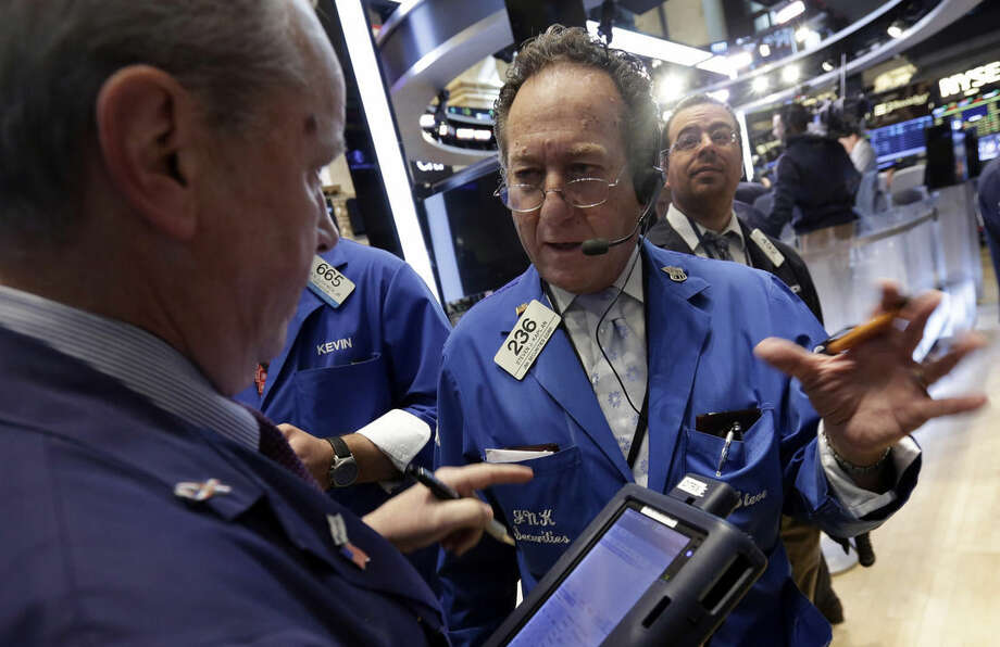 Trader Steven Kaplan, foreground right, works on the floor of the New York Stock Exchange Thursday, May 7, 2015. U.S. stocks are opening mostly lower, pushing the Dow Jones industrial average into the red for the year. (AP Photo/Richard Drew)