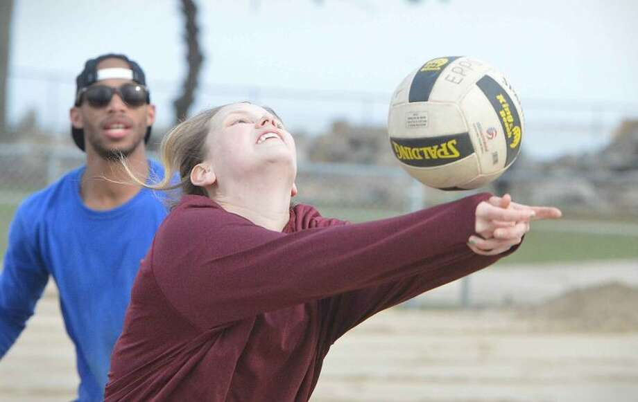 Hour Photo/Alex von Kleydorff Kristen Anderson responds to a shot from accross the net while playing volleyball with friends at Calf pasture Beach
