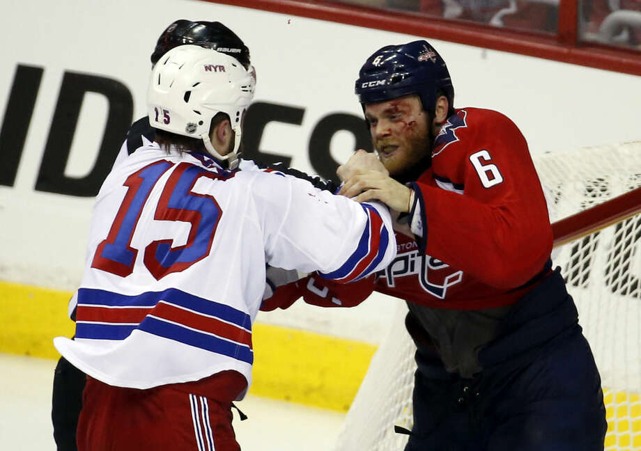 New York Rangers left wing Tanner Glass (15) fights with Washington Capitals defenseman Tim Gleason (6) during the third period of Game 4 in the second round of the NHL Stanley Cup hockey playoffs, Wednesday, May 6, 2015, in Washington. The Capitals won 2-1. (AP Photo/Alex Brandon)