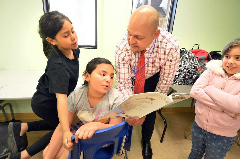 Hour Photo/Alex von Kleydorff Dr. Reese Morales reads to the class and Anny Canahui, Gezelle Osequera, and Maria Gutierrez during the After the Bell program at SoNo Community Center