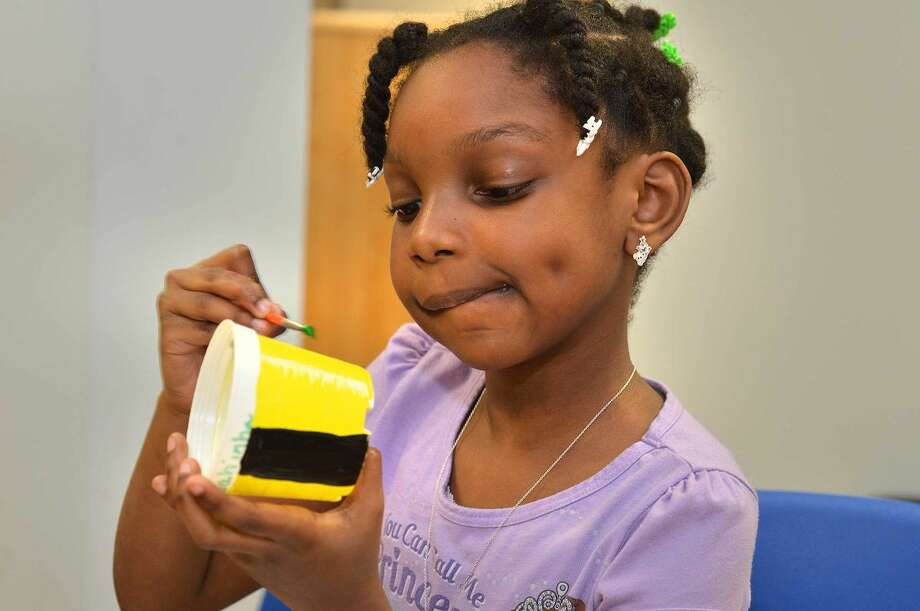 Hour Photo/Alex von Kleydorff Sahinha Pierre concentrates on the design she is painting on her planter during the After the Bell program at SoNo Community Center