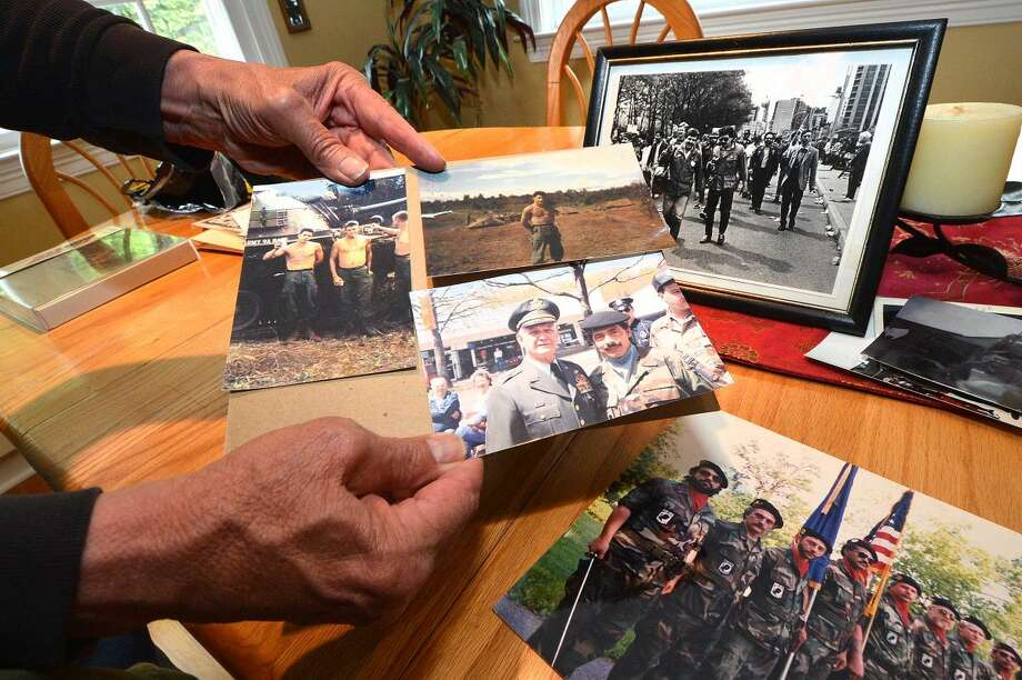 "Vietnam veteran Ralph Del Vecchio holds a few of the photos from his service during the war. The front photo shows him with U.S. General William Westmoreland at the Darien Memorial Day Parade in the mid-1990s. Above, framed, is him marching with other Vietnam veterans down the ""Canyon of Heroes"" in New York City in 1984."
