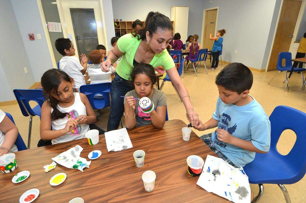 Hour Photo/Alex von Kleydorff Teachers Aid Annamilena Moreno helps kids with their paintng projects during the After the Bell program at SoNo Community Center