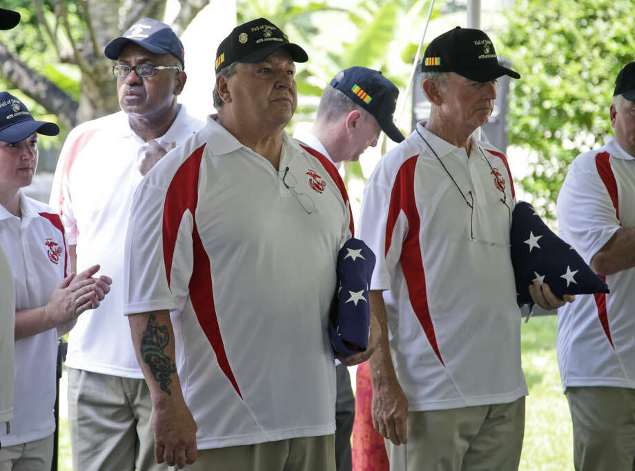 Former Marine Sgt. John Ghilain of Malden, Massachusets, left, and Sgt. Kevin Maloney of Hollywood, Florida, hold U.S. flags during the unveiling ceremony of a plaque dedicated to their fallen comrades Cpl. Charles McMahon and Lance Cpl. Darwin Judge who were the last U.S. servicemen killed in the Vietnam War, at the U.S. Consulate in Ho Chi Minh City, Vietnam, Thursday, April 30, 2015. On the 40th anniversary of the fall of Saigon on Thursday, a group of Marines who were there that day returned to what is now Ho Chi Minh City for a memorial ceremony at the site of the old embassy, which is now the U.S. Consulate. They had been in charge of guarding the embassy and the defense attache office beside Tan Son Nhat Airport, and were tasked with helping to get the last Americans out. (AP Photo/Dita Alangkara)