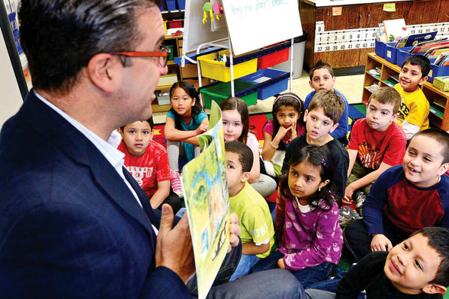 "Hour photo / Erik Trautmann NBC Universal General Manager and executive in charge of production, Vinnie Fusco, visits the Toquam Magnet School in Stamford Tuesday to read to Cathy Austin's first-grade class as part of The Volunteer Center of United Way of Western Connecticut's Annual ""Business to Books"" Read-a-thon."