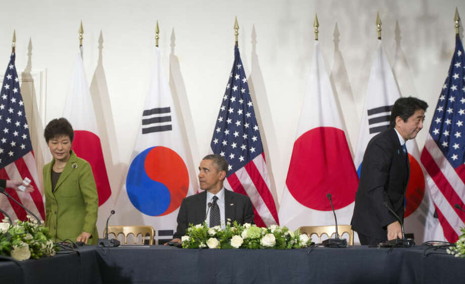 FILE - In this March 25, 2014 file photo, U.S. President Barack Obama, center, watches South Korean President Park Geun-hye, left, and Japanese Prime Minister Shinzo Abe, right, move to their seats at the opposite ends of the table to start their trilateral meeting shortly after they sat together with Obama to speak to the press at the U.S. Ambassador's Residence in the Hague, Netherlands. The U.S. has 50,000 troops in Japan and about 28,500 deployed in South Korea, where it just concluded joint U.S.-South Korean exercises. But Tokyo and Seoul remain at odds over a separate territorial dispute and lingering Korean resentment of Japanese aggression before and during World War II. (AP Photo/Pablo Martinez Monsivais, File)