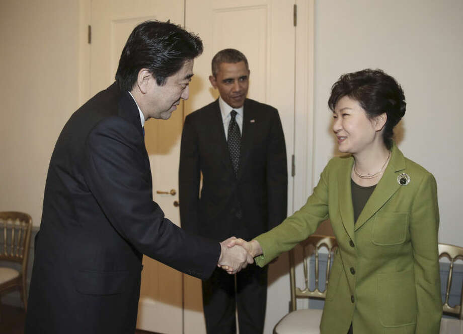 FILE - In this March 25, 2014 file photo, South Korean President Park Geun-hye, right, shakes hands with Japanese Prime Minister Shinzo Abe, left, as U.S. President Barack Obama looks on before their trilateral meeting at the U.S. Ambassador's Residence in the Hague, Netherlands. Obama's travels through Asia this week will underscore the renewed U.S. commitment to the region, with an eye both to China's rising assertiveness and to the fast-growing markets that are the center of gravity for global growth. (AP Photo/Yonhap, Do Kwang-hwan) KOREA OUT
