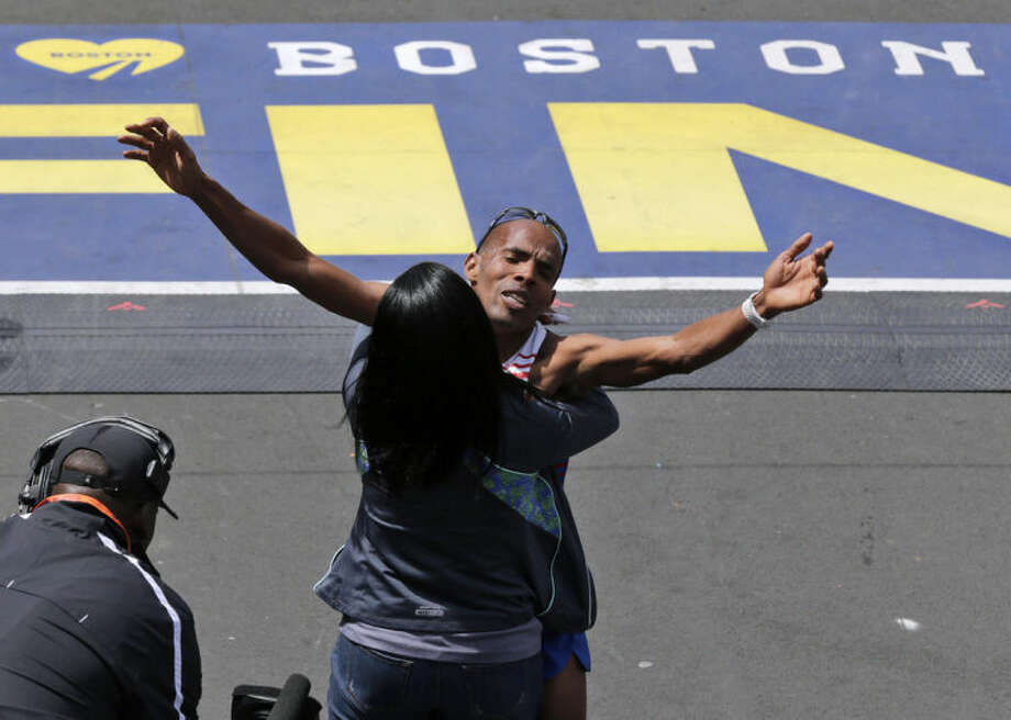 Meb Keflezighi, of San Diego, Calif., is hugged after crossing the finish line to win the 118th Boston Marathon Monday, April 21, 2014 in Boston. (AP Photo/Charles Krupa)