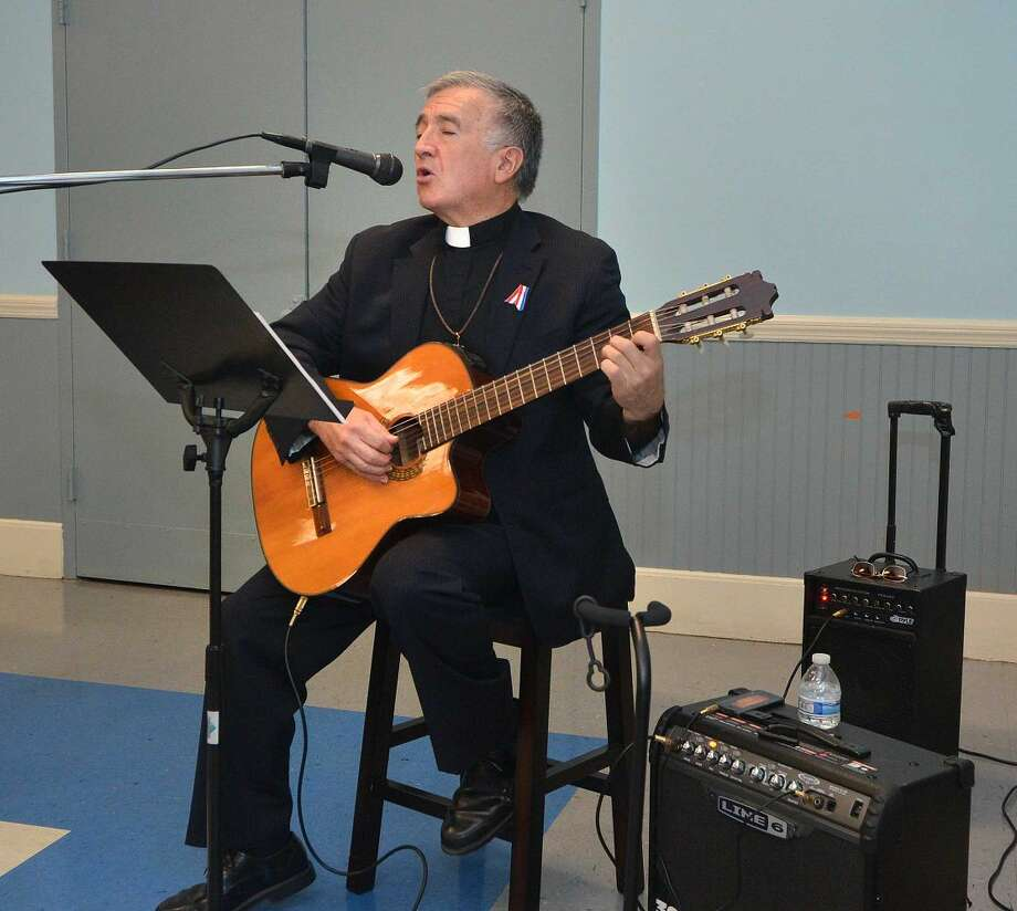 Hour Photo/Alex von Kleydorff Pastor Oscar DeStruge plays guitar and sings Bind us Together during the observance of the National Day of Prayer at a service at the SoNo Community Center Thursday