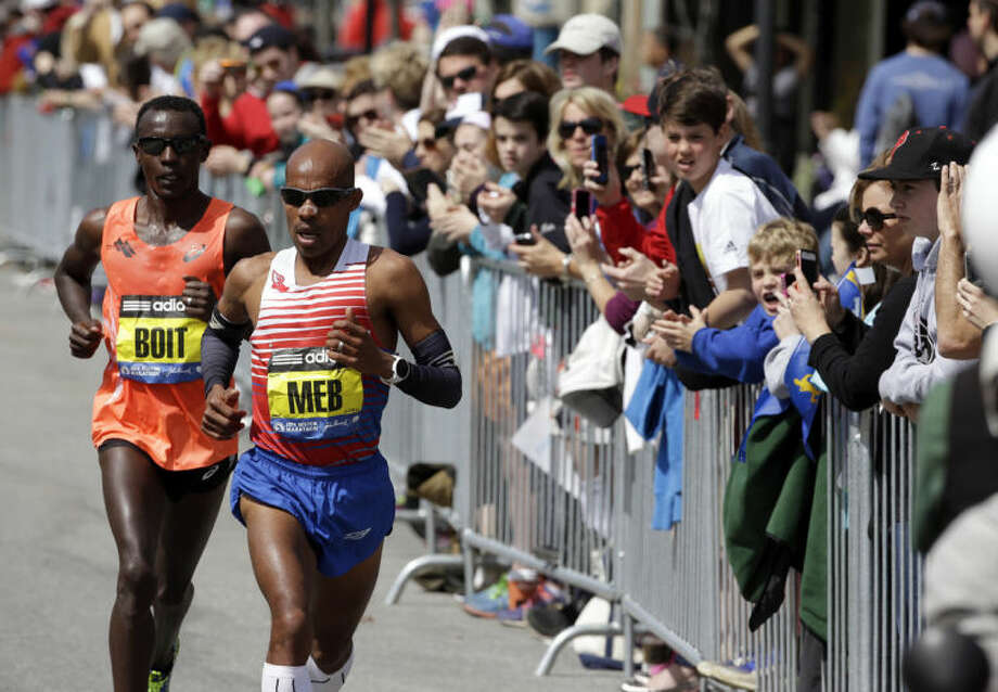 Josphat Boit, left, and Meb Keflezighi, compete along the course of the 118th Boston Marathon Monday, April 21, 2014 en route to Boston. (AP Photo/Steven Senne)