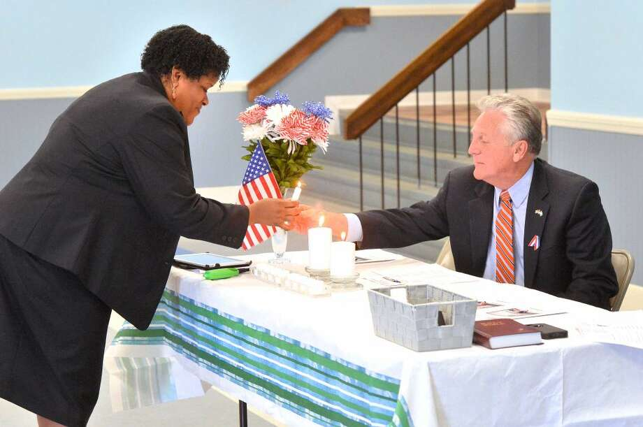 Hour Photo/Alex von Kleydorff Pastor Ronel Howard and Mayor harry rilling light a candle during the observance of the National Day of Prayer at a service at the SoNo Community Center Thursday