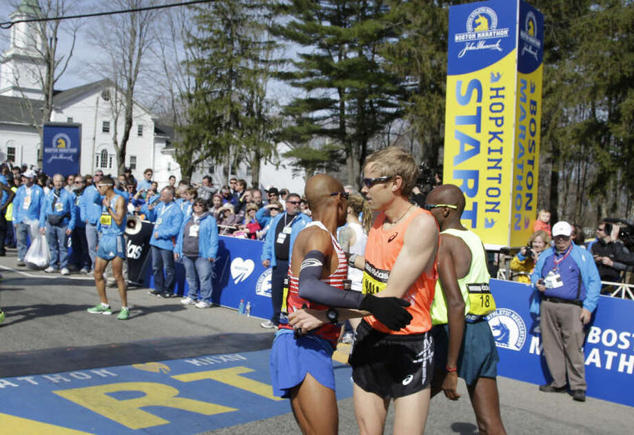Runners Meb Keflezighi, and Ryan Hall, right, of the United States, wish each other well before the start of 118th Boston Marathon Monday, April 21, 2014, in Hopkinton, Mass. (AP Photo/Stephan Savoia)