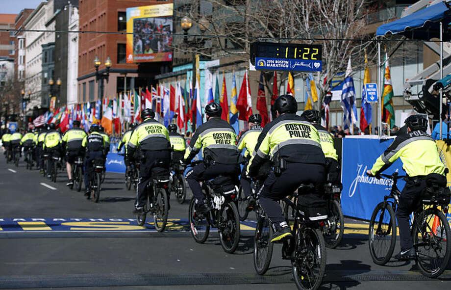 Boston Police officers on bicycles ride across the finish line before the 118th Boston Marathon Monday, April 21, 2014 in Boston. (AP Photo/Elise Amendola)