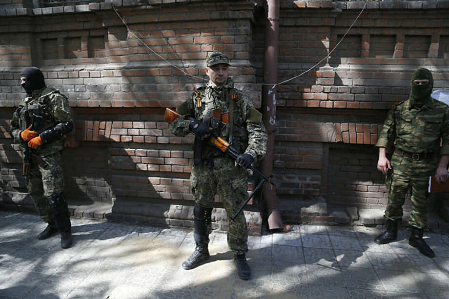 Armed Pro-Russian men on the street in Slovyansk, eastern Ukraine, Monday, April 21, 2014. The self-proclaimed mayor of Slovyansk in eastern Ukraine is appealing to Russia to send in peacekeeping troops after a shootout at a checkpoint near the city manned by pro-Russia insurgents. (AP Photo/Sergei Grits)
