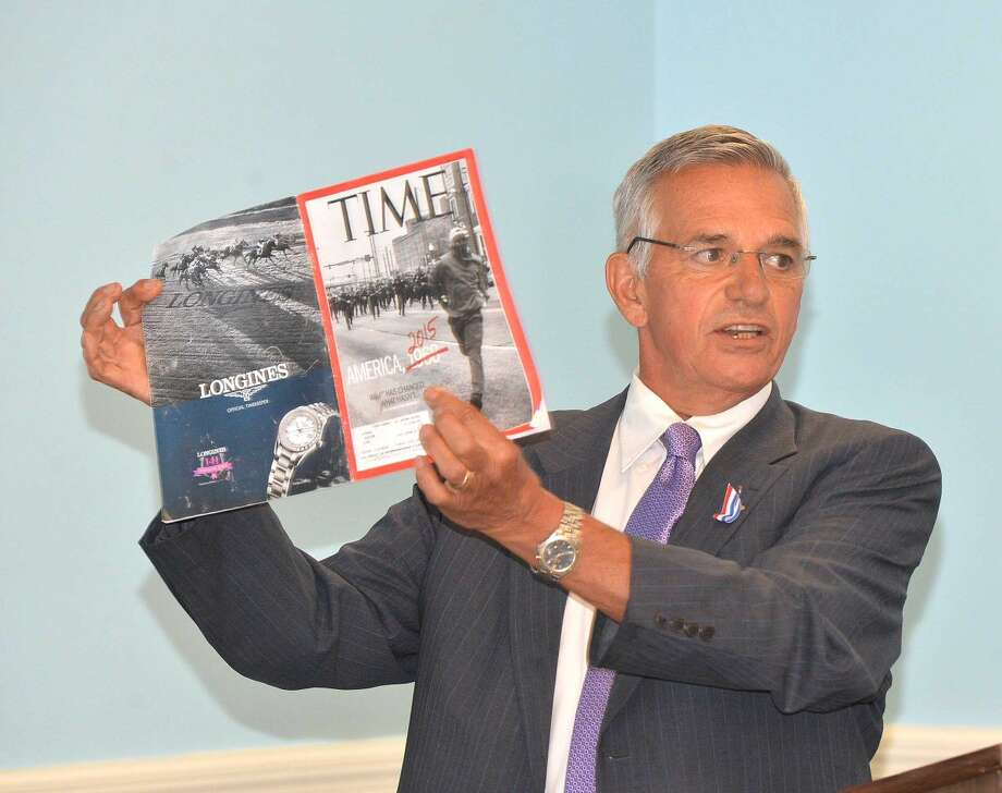 Hour Photo/Alex von Kleydorff Rev Randy Day shows a Time Magazine to make a point about injustice and people impacted by racism during the observance of the National Day of Prayer at a service at the SoNo Community Center Thursday