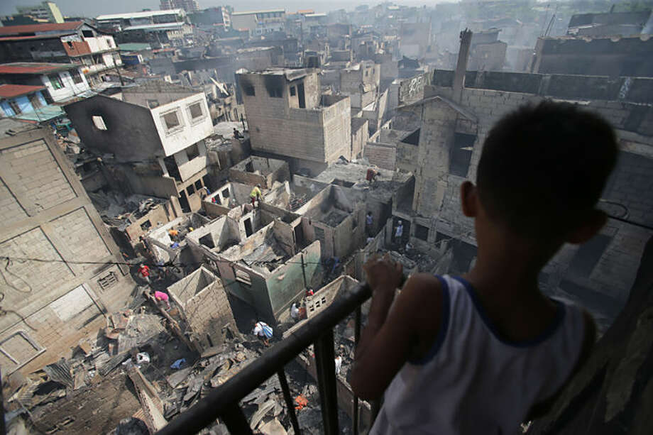 A young Filipino resident looks at burned houses after a fire broke out at a slum area in Caloocan city, north of Manila, Philippines, Monday, April 21, 2014. Several hundred families went homeless after the fire which happened late Sunday. (AP Photo/Aaron Favila)