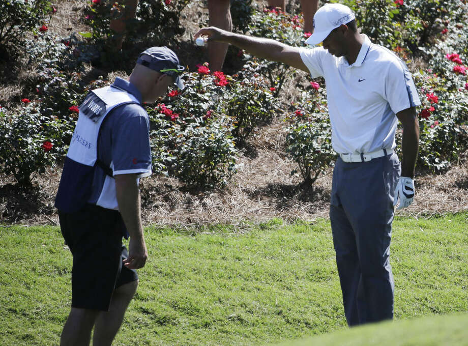 Tiger Woods takes a drop after his ball went in the water off the eighth fairway during the first round of The Players Championship golf tournament Thursday, May 7, 2015, in Ponte Vedra Beach, Fla., Fla. To the left is Woods caddie Joe LaCava. (AP Photo/Chris O'Meara)