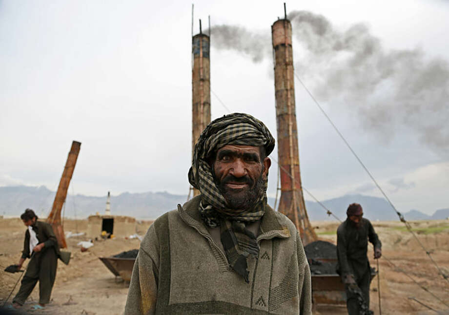 Mohammad Malook 55, poses for a photograph as he works at a brick factory on the outskirts of Kabul, Afghanistan, Monday, April 21, 2014. Men generally work for 8 hours a day, six days a week, and make about 350 Afghani ($6) per day. (AP Photo/Rahmat Gul)
