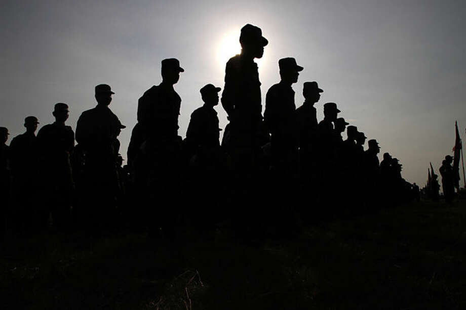 """Cambodian army soldiers stand while participating in a U.S.-backed peacekeeping exercise dubbed """"Angkor Sentinel 2014"""" at the Cambodian tank command headquarters in Kampong Speu province, 60 kilometers (37 miles) west of Phnom Penh, Cambodia, Monday, April 21, 2014. The U.S. and Cambodia on Monday commenced Angkor Sentinel, an annual military exercise designed to promote regional peace and security. (AP Photo/Heng Sinith)"""