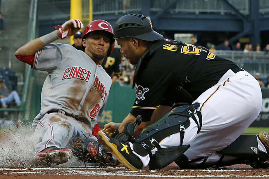 Cincinnati Reds' Billy Hamilton (6) scores ahead of the tag by Pittsburgh Pirates catcher Russell Martin (55) during the first inning of a baseball game in Pittsburgh Monday, April 21, 2014. Hamilton scored on a fielder's choice by teammate Brandon Phillips. (AP Photo/Gene J. Puskar)