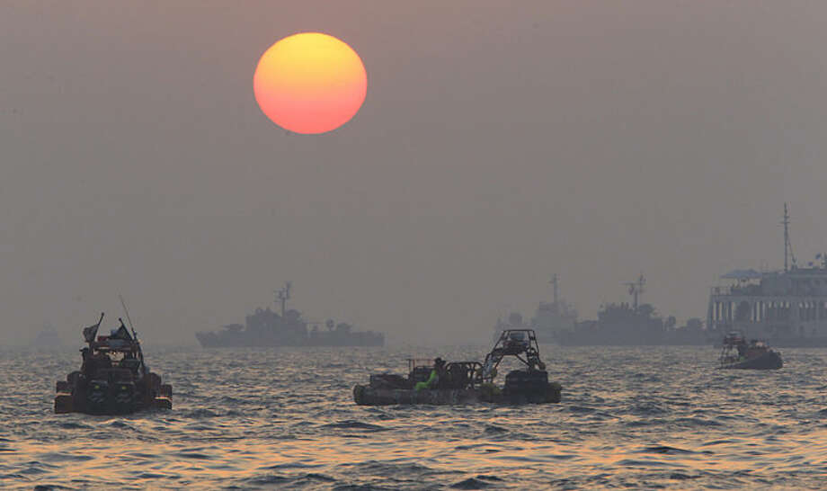 The orange sun begins to set above searchers and divers looking for bodies of passengers believed to have been trapped in the sunken ferry Sewol in the water off the southern coast near Jindo, south of Seoul, South Korea, Tuesday, April 22, 2014. One by one, coast guard officers carried the newly arrived bodies covered in white sheets from a boat to a tent on the dock of this island, the first step in identifying a sharply rising number of corpses from the South Korean ferry that sank nearly a week ago. (AP Photo/Ahn Young-joon)
