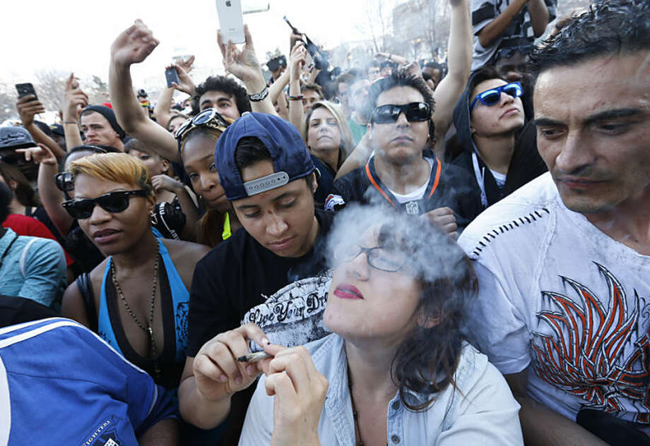 Partygoers listen to live music and smoke pot on the second of two days at the annual 4/20 marijuana festival in Denver, Sunday, April 20, 2014. The annual event is the first 420 marijuana celebration since retail marijuana stores began selling in January 2014. (AP Photo/Brennan Linsley)