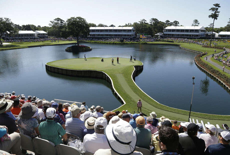 Jimmy Walker, second from left on the green, lines up his putt on the 17th green during the first round of The Players Championship golf tournament Thursday, May 7, 2015 in Ponte Vedra Beach, Fla. (AP Photo/Lynne Sladky)