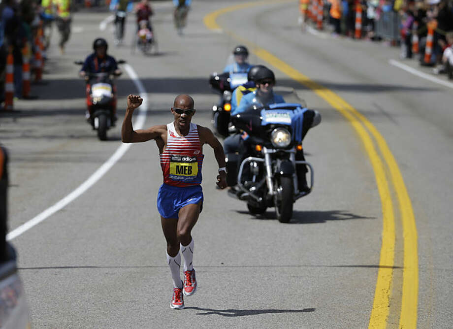 Meb Keflezighi, of San Diego, Calif., raises his fist as he competes in the 118th Boston Marathon Monday, April 21, 2014 in Newton, Mass. (AP Photo/Steven Senne)