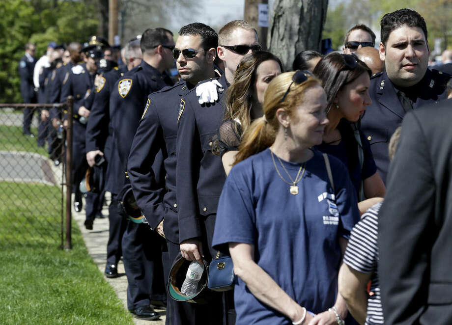 People wait in line to pay their respects during the wake for New York City police officer Brian Moore Thursday, May 7, 2015, in Bethpage, N.Y. Moore died Monday after being shot in the head while on duty last Saturday. The 25-year-old and his partner had stopped a man suspected of carrying a handgun when the man opened fire on them. (AP Photo/Seth Wenig)
