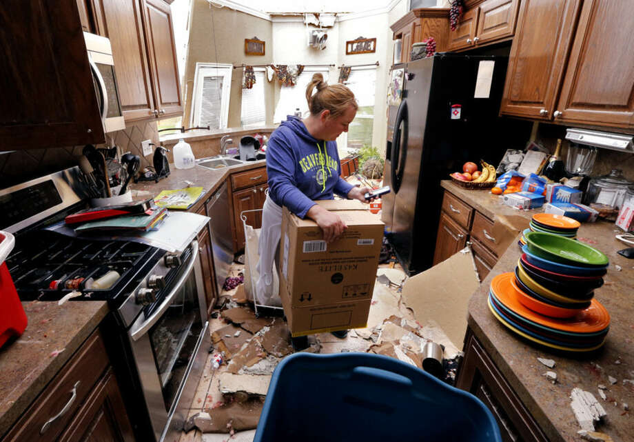 Jennifer Moon recovers kitchen items by the light of the sky on Thursday, May 7, 2015, in Bridge Creek, Okla. Wednesday's storm took off the roof. (Steve Sisney/The Oklahoman via AP)