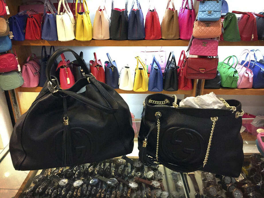 In this March 11, 2015 photo, counterfeit branded bags appear on display in a room hidden from the public area of a popular shopping mall in Beijing. A review of hundreds of pages of court documents from cases in the United States and China, along with interviews with lawyers, investigators, government officials and industry representatives, show that a lack of legal cooperation between the West and China is allowing counterfeiters to use Chinese banks as financial shelters. (AP Photo/Mark Schiefelbein)