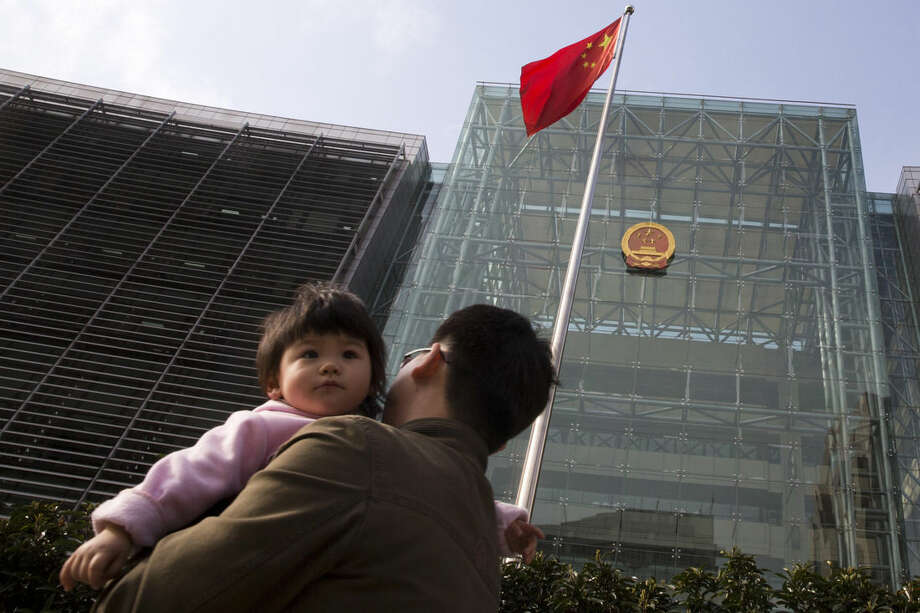 In this Monday, March 23, 2015 photo, a man carries a child past the Shanghai High People's Court. Foreign companies have successfully used China's courts, winning 90 percent of the intellectual property cases they filed in a Shanghai court over the last five years, according to Rui Wenbiao, an intellectual property judge. But these efforts remain orders of magnitude smaller than the problem, numbers show. (AP Photo/Ng Han Guan)