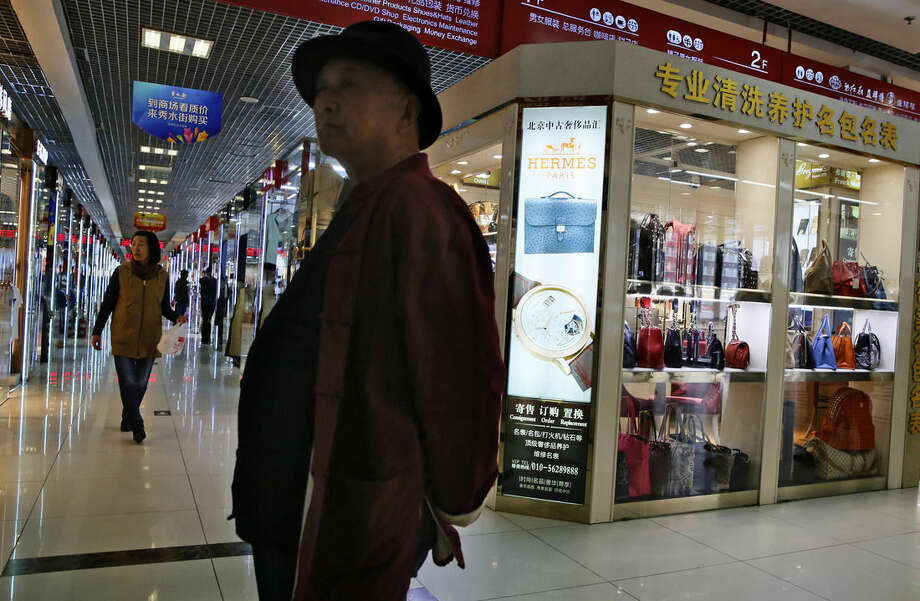 In this Wednesday, April 8, 2015 photo, customers walk near a shop selling refurbished or second hand items from brands such as Gucci, Chanel and Cartier at the Silk Street market in Beijing. (AP Photo/Ng Han Guan)