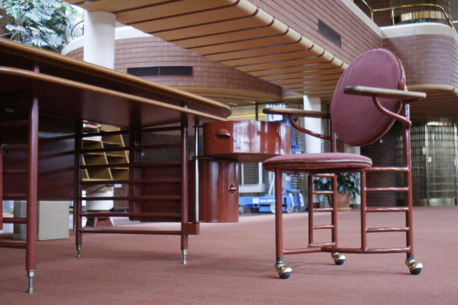 This Friday, April 18, 2014, photo shows an original desk and a three-legged chair designed by architect Frank Lloyd Wright for workers at the SC Johnson Administration Building in Racine, Wis. Most employees' chairs were later modified to have four legs because employees kept tipping over. (AP Photo/M.L. Johnson)